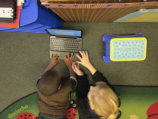 Fifth grade student teaches a younger student how to use a Chromebook